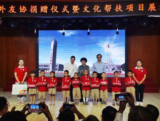 林松添會長(后排右一)向小朋友發放兒童衛生防護包。安利供圖