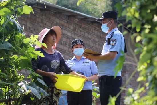 图为酷暑之下民警走社区访民意。九龙坡警方供图