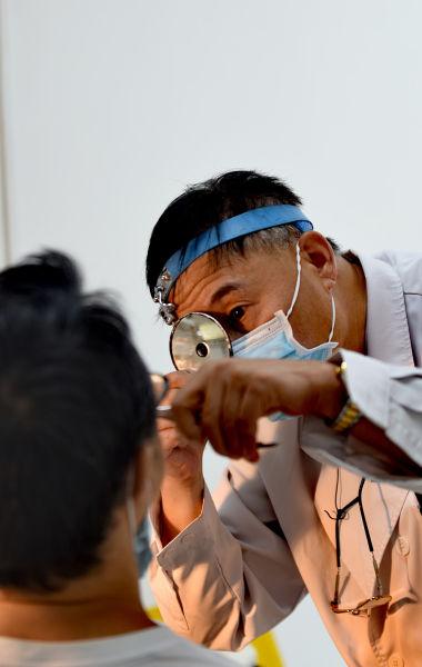 图为耳鼻咽喉科主任医师杨桦通过额戴反光镜为患者仔细检查鼻腔内病情。新桥医院供图