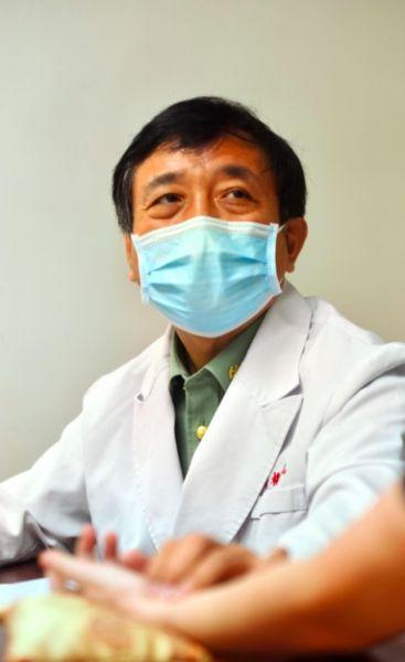 图为中医科主任医师晋献春正在认真为患者把脉、耐心询问患者病情。新桥医院供图