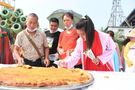 图为工作人员和游客一同分享巨型月饼。陈超 摄