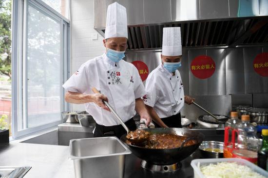 图为社区食堂厨师正在做菜。郭旭 摄