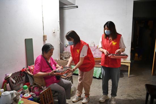 图为社区志愿者为行动不便利的老人送餐。 郭旭 摄