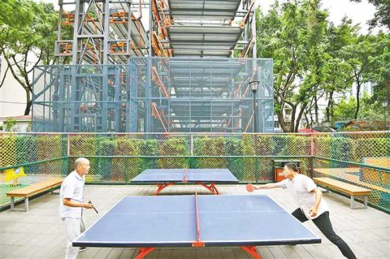 9月6日,九龙坡区白马凼小区街心花园,居民在迷你循环塔机械停车楼旁打乒乓球。记者 谢智强 摄/视觉重庆