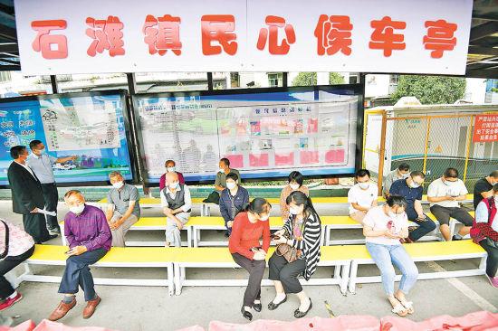 9月9日,巴南区石滩镇公交车站民心候车亭,居民坐在长条凳上等候班车。记者 谢智强 摄/视觉重庆