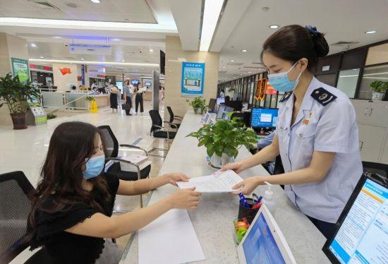 重庆市渝中区税务局工作人员为纳税人办理跨区(县)迁移事项。何涵雯 摄