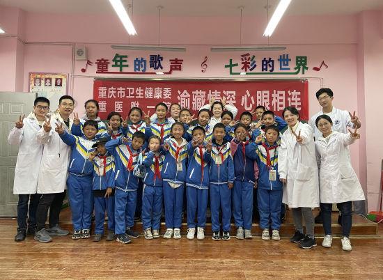 图为援藏医疗队与西藏青少年合影留念。重庆医科大学供图
