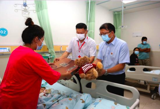 图为刘祖礼和张维斌为患儿家属赠送礼物。重庆红十字会供图