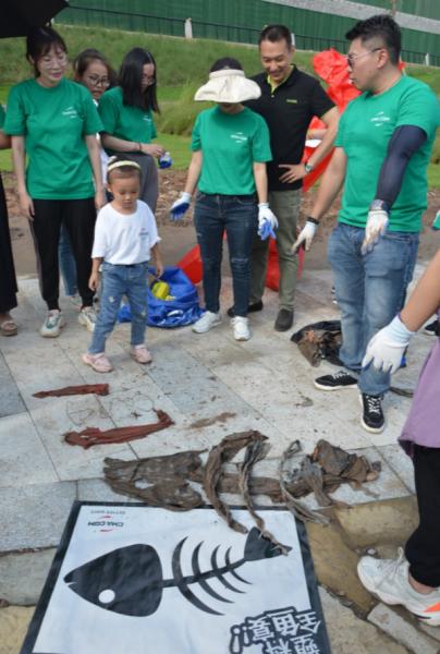 """图为志愿者用捡回来的垃圾制作""""全鱼宴""""。达飞集团供图"""