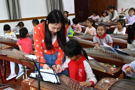 图为老师教学生弹古筝。两江新区康庄美地小学供图