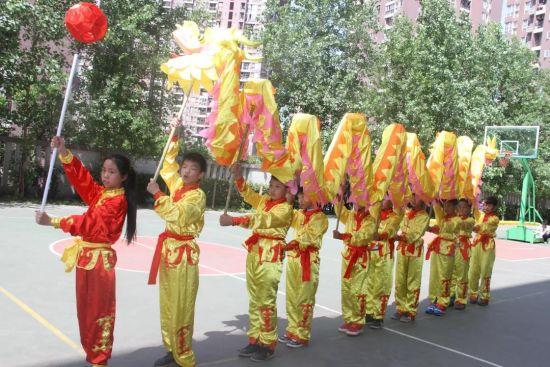 图为小学生学习舞龙。两江新区康庄美地小学供图