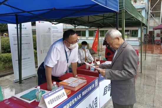 图为重庆移动工作人员向市民推广国家反诈中心APP。