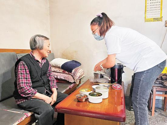 吴艳艳为陈文英老人(左)送去一天的饭菜。