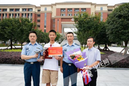 重庆市2017年高考第一份录取通知书,8日下午送到了考生李成林(左二)手图片